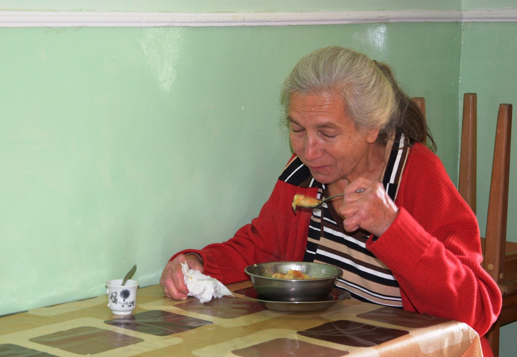 An old woman sits at a table eating a hot meal