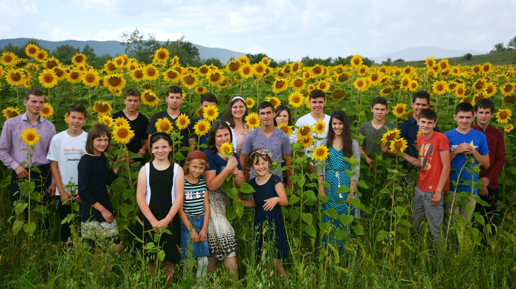 Children and young people of Casa Ray stand in a sunflower field